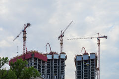 Lift tower cranes on construction site against background of the blue sky, houses new buildings near a residential area Stock Image
