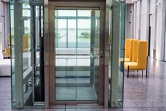 Lift with transparent glass doors in modern building. Close up of modern elevator with transparent doors in business building royalty free stock photo
