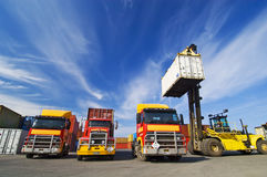 Lift truck loading shipping containers onto trucks Royalty Free Stock Images
