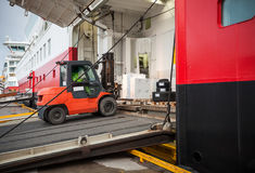 Lift truck unloads big passenger ship Royalty Free Stock Image
