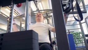 Lift-wegende machine wordt gebruikt in een gymnastiek door een gehandicapte mens terwijl het praktizeren stock footage