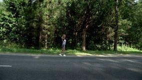 Lifta kvinnan med ryggsäcken på vägen på förbakgrund arkivfilmer