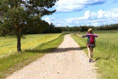 Lifta väglopp Kvinna med en stor ryggsäck som försöker att stoppa en ritt, genom att tumma Royaltyfri Bild