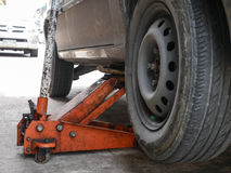 Lifted car by car jack tool for maintenance and repair. Stock Photography