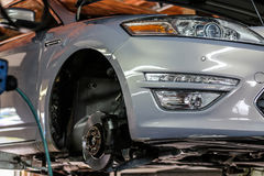 Lifted car without wheel in mechanic garage Stock Photo