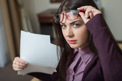 She lifted her glasses. And holding a piece of paper stock image