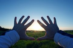 Lifted up hands in the background of the sunset Stock Image