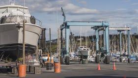 Liften voor schepen op de jachthaven met een boot op één van hen en een groot schip in de voorgrond Stock Foto's