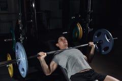 Lifter веса на жиме лёжа поднимая штангу на стенде уклона Стоковые Изображения RF
