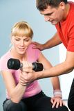 Lifting barbell. Image of experienced instructor helping young lady lift barbell in the gym Royalty Free Stock Photography