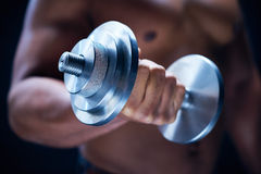 Lifting barbell. Close-up of male hand holding metal barbell stock photography