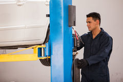 Lifting a car at an auto shop. Handsome young mechanic operating a car lift to raise up a car before fixing it at an auto shop Royalty Free Stock Image
