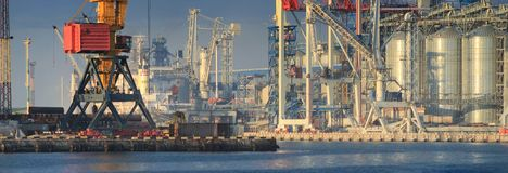Lifting cargo cranes, ships and grain dryer in Sea Port stock photography