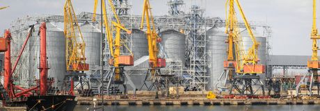Lifting cargo cranes, ships and grain dryer in Sea Port of Odessa stock photos