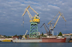 Lifting cargo cranes at the shipyard in Bay of Black Sea. Stock Photography