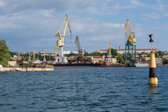 Lifting cargo cranes at the shipyard in Bay of Black Sea. Stock Photo