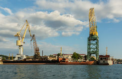 Lifting cargo cranes at the shipyard in Bay of Black Sea. Royalty Free Stock Photography