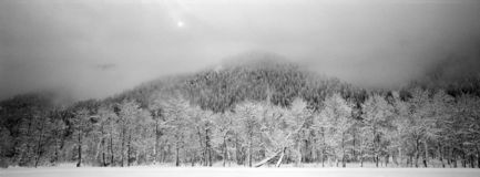 Lifting Clouds After a Snow Storm. The sun tries to break through storm clouds that have blanketed Aspen with snow. Panoramic black and white royalty free stock images