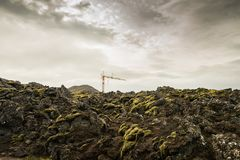 Lifting construction crane among the rocky terrain covered with lava and moss. Stock Photo
