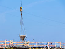 Lifting crane delivers concrete bucket to construction site to p Stock Photo