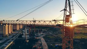 Lifting crane standing in a construction area, building area, site area from above. Construction Site At Sunset 4K. Static lifting crane standing in a building stock video footage