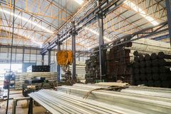 Lifting crane with yellow hook in steel pipe. Warehouse Stock Photo