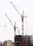 Lifting cranes over frame-house Stock Photos