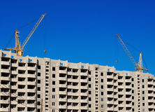 lifting cranes over new apartment hous Royalty Free Stock Photos