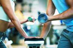 Lifting the dumbbells. A man and a woman (only arms and body) lifting dumbbells (focus on dumbbell, shallow depth of field Stock Images