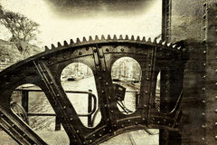 Lifting Gear of Drawbridge. Detail of the lifting gear of drawbridge over the canal in Amsterdam. Street View with bikes, boats and city life through the Stock Photo