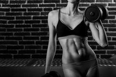 Lifting for health. Cropped black and white shot of a fitness woman. Lifting weights against a brick wall Royalty Free Stock Photography