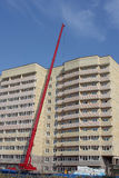 Lifting hydraulic crane on construction of multistory building Stock Images