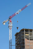 Lifting mechanism construction crane. Construction crane delivers the concrete to build a house Royalty Free Stock Image