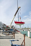 Lifting sailing boat in the water. With crane in the harbour Royalty Free Stock Image