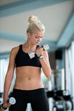 Lifting some weights and working on her biceps in a gym Royalty Free Stock Photo