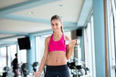 Lifting some weights and working on her biceps in a gym Royalty Free Stock Images