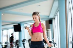 Lifting some weights and working on her biceps in a gym Stock Images