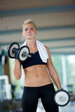 Lifting some weights and working on her biceps in a gym Stock Image