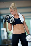 Lifting some weights and working on her biceps in a gym Stock Photography