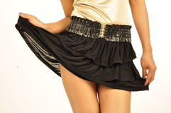 Lifting up her black skirt. Young woman lifting up the hemline of her skirt Royalty Free Stock Image