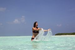 Lifting water. Girl in turquoise blue water playing with water Royalty Free Stock Images