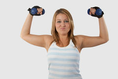 Lifting Weights. Young pretty blond woman in workout attire facing forward while holding and lifting two three pound weights with a funny facial expression stock photos