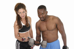 Lifting Weights. Attractive woman and handsome man lifting weights together.  Isolated shot on white Royalty Free Stock Photography