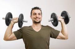 Lifting weights. Casual man lifting dumbells in studio shot Royalty Free Stock Photo