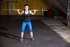 Lifting weights in a gym. Cute Hispanic girl doing some squats with a barbell in a gym Stock Photo