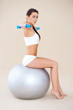 Lifting weights while sitting on fitness ball Royalty Free Stock Photo