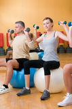 Lifting weigths on a fitness ball Stock Image