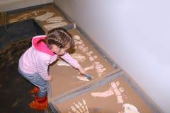 Liftle-Mädchen im Rosa mit Bürste gräbt in der Hand Knochen Lizenzfreie Stockbilder