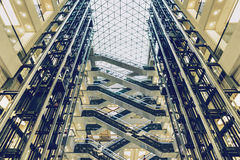 Lifts and escalators in a modern building, view of modern shopping mall. Lifts and escalators in a modern building, interior view of modern shopping mall, toned Stock Photos