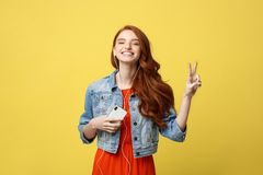Liftstyle: Retrato de una mujer caucásica sonriente bonita en auriculares que escucha la música y que muestra gesto de la paz Foto de archivo